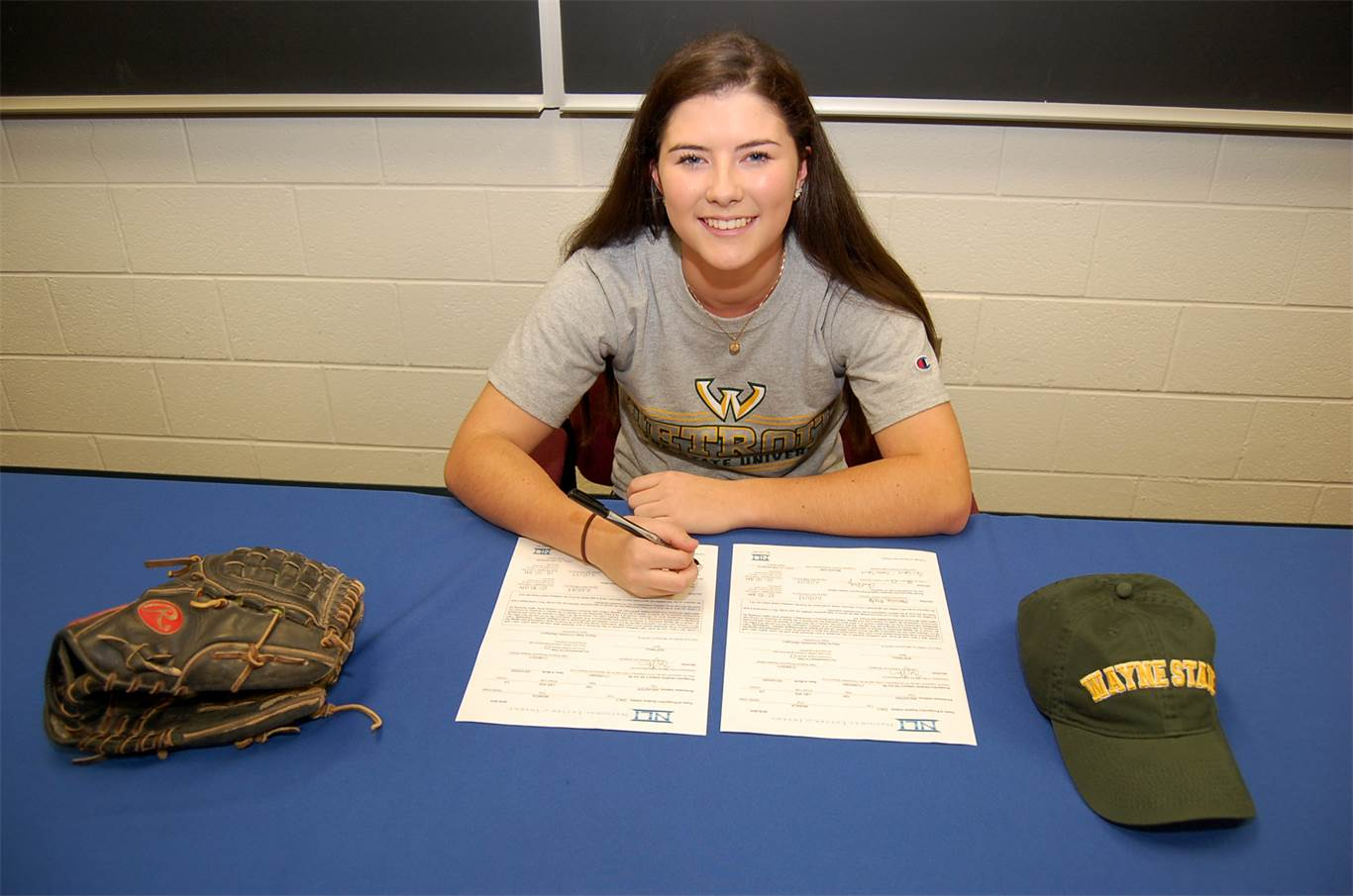 Monica Daly signs her letter of intent to attend Wayne State University on a softball scholarship with family, coaches and teammates at St. Mary Catholic Secondary School on Nov. 10.