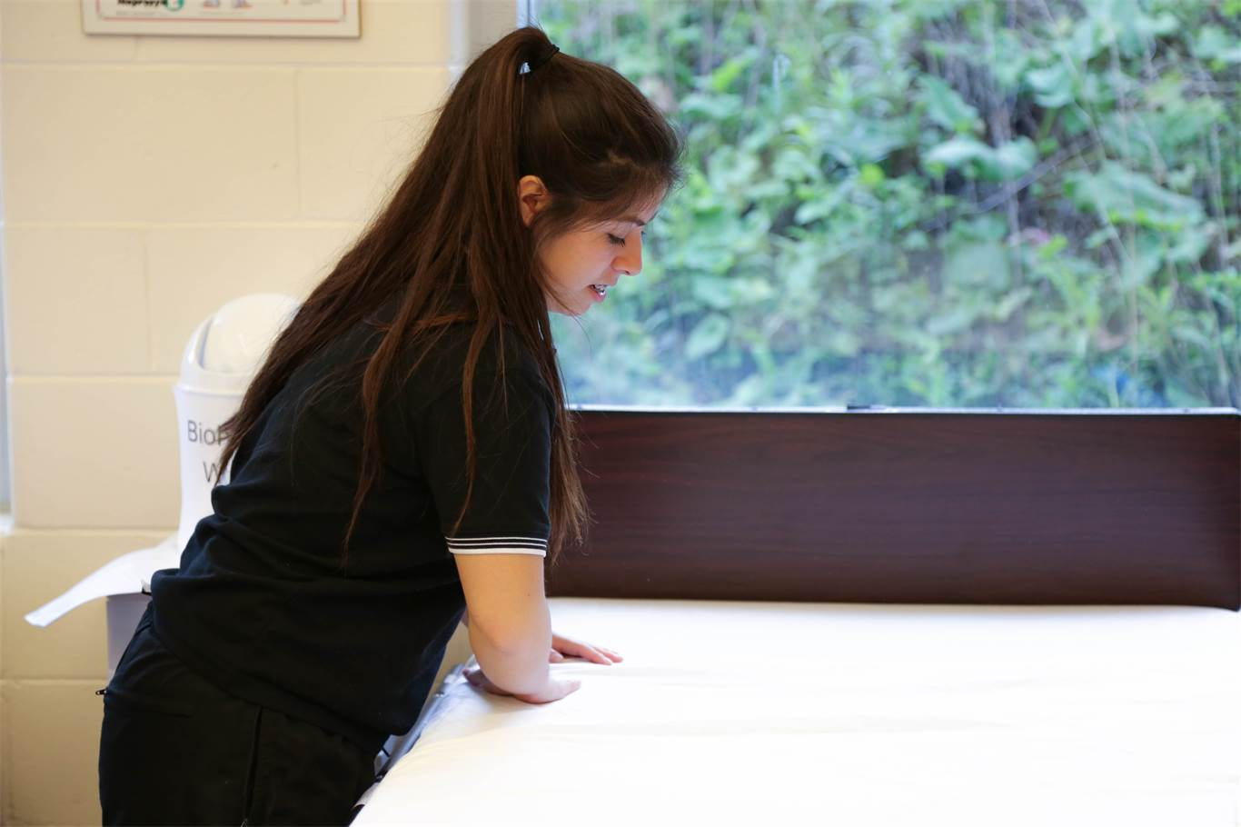 When making a bed, students learn to smooth out wrinkles to lessen irritation from a patient's ulcers.