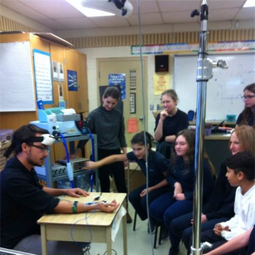 Students test reaction using a Transcranial Magnetic Stimulation machine.